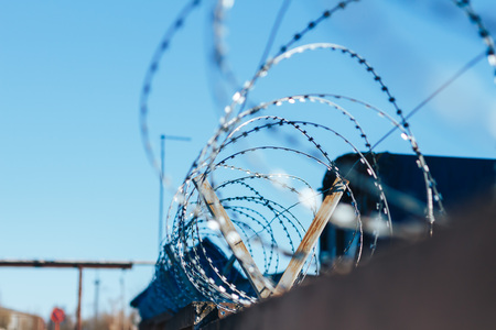 Barbed wire on top of the concrete fence with blue sky with clouds closeup Stock Photo