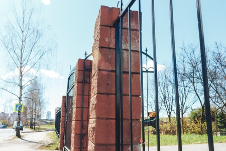 High fence with brick columns. Black Railings and brick wall.