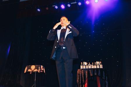 MINSK, BELARUS November 4 2017 International Illusion Festival MAGIC 2017 A male magician shows a presentation with a bottle