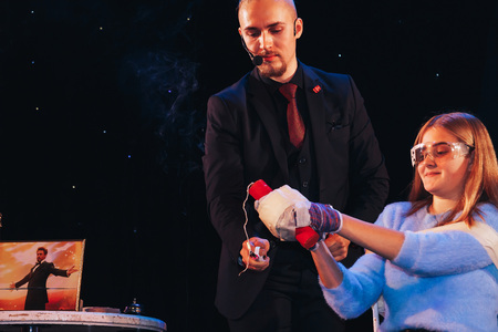 MINSK, BELARUS November 4 2017 International Illusion Festival MAGIC 2017 A young magician takes an assistant girl