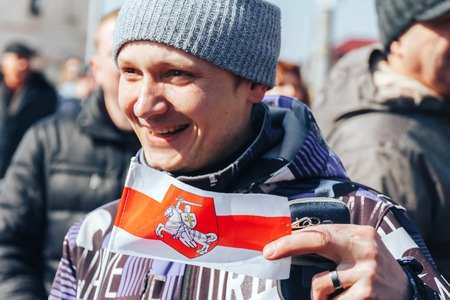 Minsk, Belarus. March 25, 2018 A holiday dedicated to the 100th anniversary of the founding of the Belarusian Peoples RepublicThe man is standing outdoors Editorial