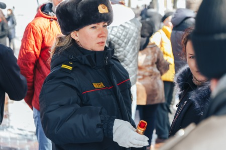 Minsk, Belarus. March 25, 2018 A holiday dedicated to the 100th anniversary of the founding of the Belarusian Peoples Republic A policewoman holding a gas canister Editorial