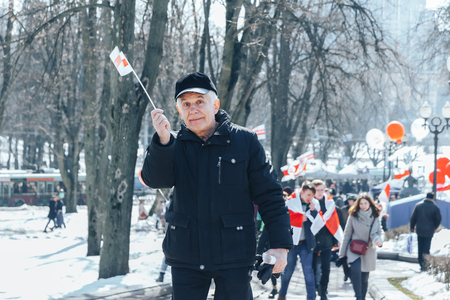 Minsk, Belarus. March 25, 2018 A holiday dedicated to the 100th anniversary of the founding of the Belarusian People's Republic Man holding a small flag outdoors