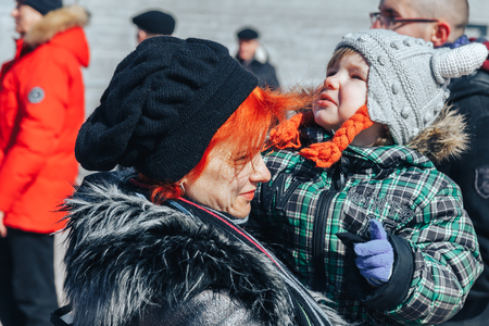 Minsk, Belarus. March 25, 2018 A holiday dedicated to the 100th anniversary of the founding of the Belarusian Peoples Republic Woman with baby stands outdoors