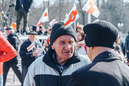 Minsk, Belarus. March 25, 2018 A holiday dedicated to the 100th anniversary of the founding of the Belarusian Peoples Republic Two elderly men with flags in caps talking outdoors Editorial