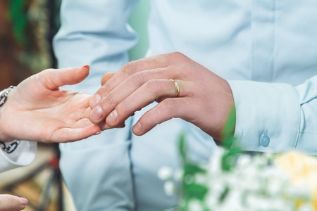 Groom with a wedding ring on his finger gently touches the hand of the bride in the registry office
