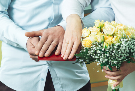 The bride and groom put their hands with wedding rings put on their fingers on the marriage registration book. Stock Photo - 119854613