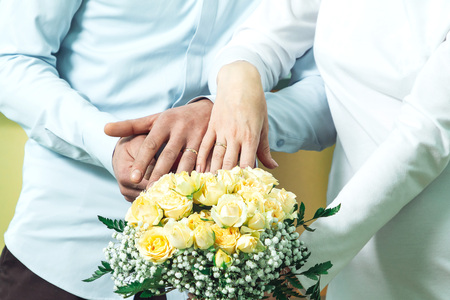 The bride and groom put their hands with wedding rings put on their fingers on the marriage registration book. Фото со стока