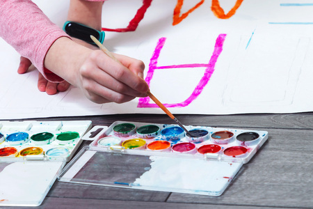 The hand of a little girl paints a poster Imagens
