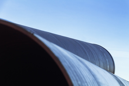 Large diameter metal pipes for water supply lie on storage areas under a blue sky