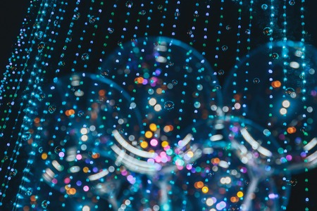 Balloons on the background of blurry lights. An image of an abstract blurred bokeh background with warm colored lights