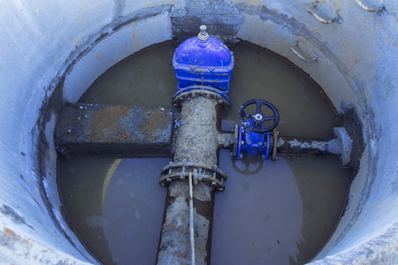 Pipeline elements, plastic pipes, concrete stop, cast-iron valve in a concrete well at the construction site Close up