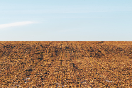 Undulating plowed field in early spring , white clouds in the blue sky Stock fotó