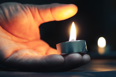 Memorial Day International Holocaust Remembrance Day On Memorial Day, a man s hand holds a candle