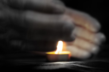 Memorial Day International Holocaust Remembrance Day On Memorial Day, a man s hand holds a candle Close up