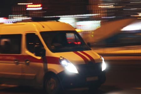 An ambulance car rides through the city at night amid glowing lights.