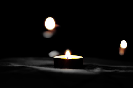 Burning candles on a black background in the day of sorrow