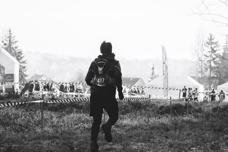 Ein Mann in einem schwarzen Anzug mit einer Trinkflasche läuft den Weg neben dem Wald entlang Schwarz-Weiß-Bild