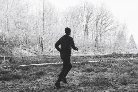 A man in a black suit with a bottle for drinking runs along the path next to the forest Black and white image