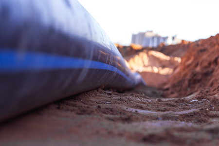 Plastic water pipe lay in a trench in the direction of residential buildings Copy space