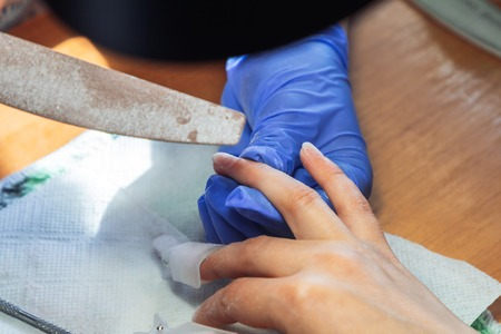A manicurist handles a woman s finger with a nail file. Other fingers of the hand are in manicure covers. Development of private business in the field of beauty and health