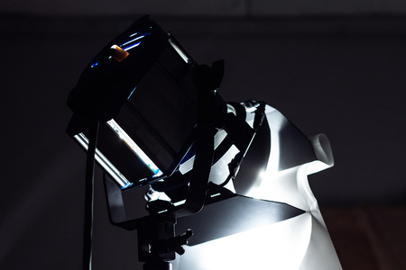 Studio spotlight for photo and video shooting costs in the dark. Copy space