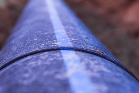 Plastic water pipe is in the trench in the direction under a blue sky residential buildings Close up