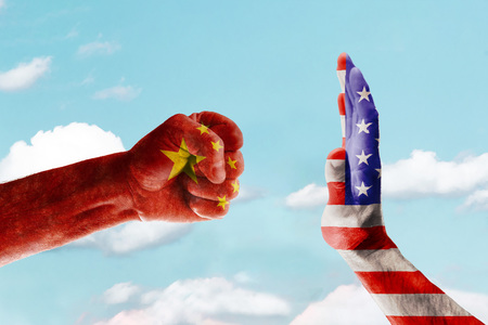 Diplomatic standoff between the United States and China. Flags are printed on hands against the blue sky.