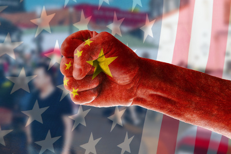 China's expansion into the US market Concept of a man's hand painted in the colors of the flag of China on the background of street trading in the blur and the US flag.
