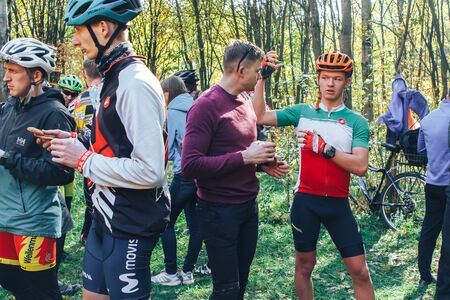 October 14, 2018, Minsk, Belarus.2018 Olympic Cross Country Cup XCO in Medvezhino Cyclists discuss the passage of the track while standing in the park 新聞圖片