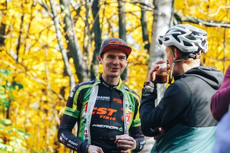 October 14, 2018, Minsk, Belarus.2018 Olympic Cross Country Cup XCO in Medvezhino Cyclists discuss the characteristics of a bike while standing in the park.