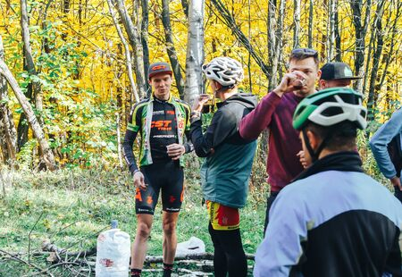 October 14, 2018, Minsk, Belarus.2018 Olympic Cross Country Cup XCO in Medvezhino Cyclists drink coffee and discuss the passage of the track after the race in the park