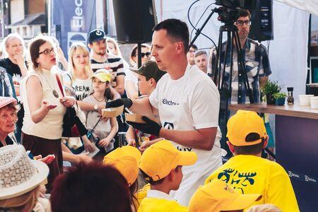June 1, 2019 Minsk Belarus Public demonstration of cooking on the street Male cook arranges tasting food among spectators at a master class