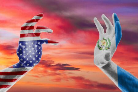 TTwo hands of a man in the colors of the flags of the USA and Guatemala against the red sky Concept USA and Guatemala signed a migration agreement.