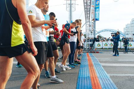 September 15, 2018 Minsk Belarus Half Marathon Minsk 2019 Athletes with phones in their hands stand before the start of the marathon. A man with a camera takes them off.