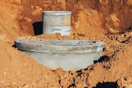Ein Betonbrunnen für die Wasserversorgung steht im Einklang mit einem anderen Brunnen und ist Teil der Wasserversorgungskette. Standard-Bild