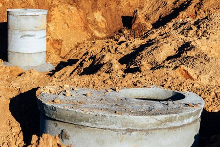 Two concrete wells covered with cement mixture for plumbing and sewer sprinkled with earth are in a deep trench