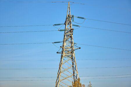 Mast of high voltage power line against blue sky