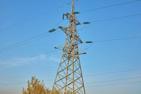 The mast of the high-voltage power line stands on the grass against the evening blue sky