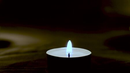 A candle burns in the dark for ritual, remembrance, celebration, sacred action, consecration, magic ritual Stock Photo