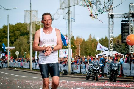 September 15, 2018 Minsk Belarus Half Marathon Minsk 2019 Mature athlete runs a marathon holding on to a fitness watch close up