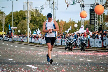September 15, 2018 Minsk Belarus Half Marathon Minsk 2019 A marathon runner looks at a fitness watch as he runs along the road