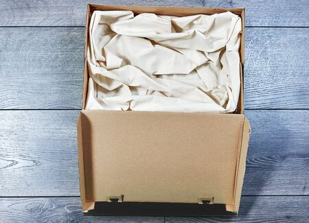 A box with white cloth inside for a pet or gift is standing on the floor Stockfoto