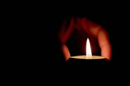 Memorial Day International Holocaust Remembrance Day On the day of the memory of the dead a hand holds a candle Burning candle in male hand, religion concept Archivio Fotografico