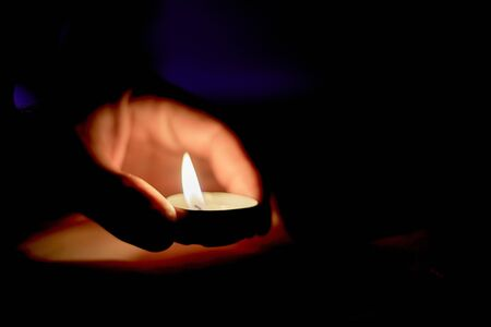 Memorial Day International Holocaust Remembrance Day On the day of the memory of the dead a hand holds a candle Burning candle in male hand, religion concept