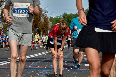September 15, 2018 Minsk Belarus A participant girl of the Minsk half marathon 2019 recovers after crossing the finish line