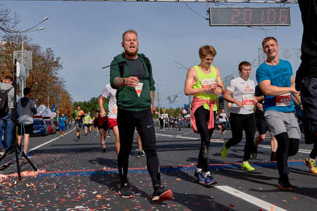 September 15, 2019 Minsk Belarus Half Marathon Minsk 2019 Crowd runners crossing the finish line marathon on paved road in town.