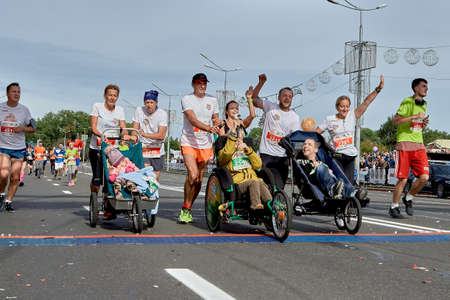 September 15, 2019 Minsk Belarus Half Marathon Minsk 2019 Happy athletes carrying disabled children in wheelchairs in front of them cross the finish line of the marathon