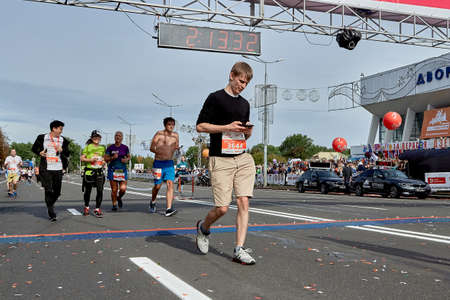 September 15, 2019 Minsk Belarus Half Marathon Minsk 2019 A participant crosses the finish line of a marathon and checks the heart rate monitor on a smartphone concept Éditoriale