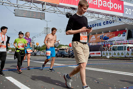 September 15, 2019 Minsk Belarus Half Marathon Minsk 2019 A young man runs behind the finish line of the marathon and checks the heart rate monitor on the concept smartphone